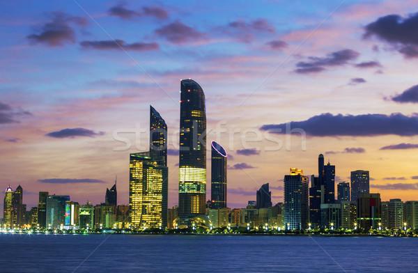 Abu Dhabi sziluett naplemente Egyesült Arab Emírségek üzlet tengerpart Stock fotó © vwalakte