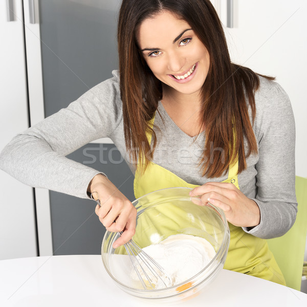 Beautiful woman whisking batter Stock photo © vwalakte