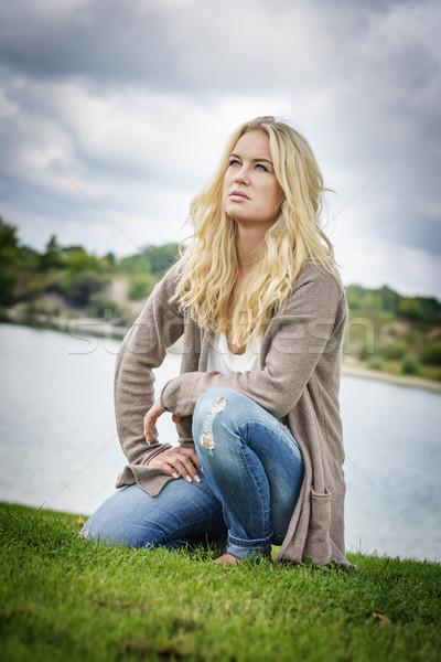 Blond woman kneeling at lake Stock photo © w20er