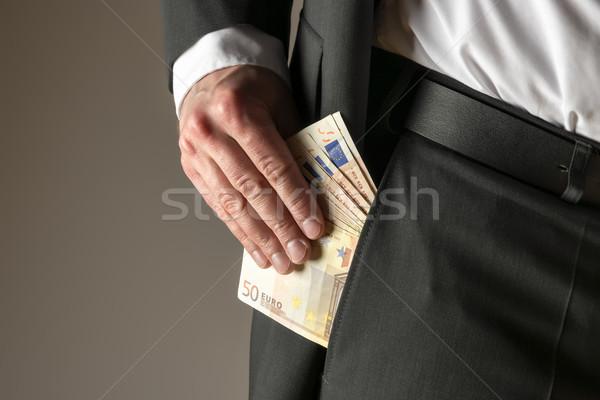 Businessman putting money in pocket Stock photo © w20er
