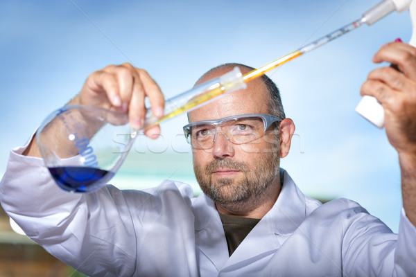 Chemist with blue liquid Stock photo © w20er