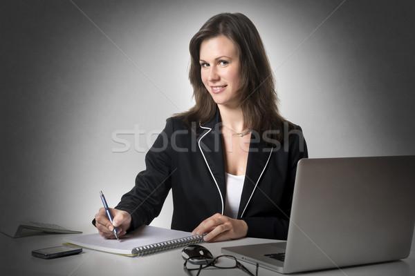 Uśmiechnięty kobieta interesu piśmie coś posiedzenia biurko Zdjęcia stock © w20er