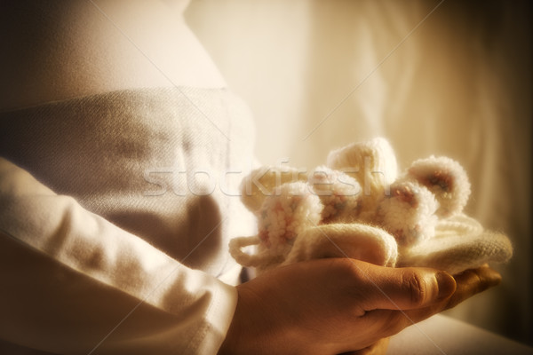 Pregnant woman is holding baby shoes Stock photo © w20er