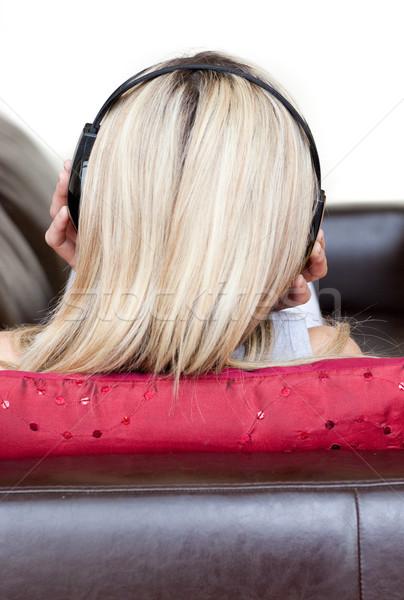 Geconcentreerde vrouw hoofdtelefoon sofa gelukkig rock Stockfoto © wavebreak_media
