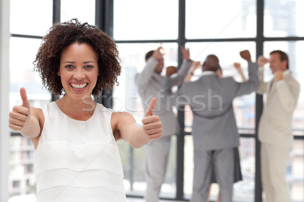 Stock photo: Successful Businesswoman doing a thum-up with his colleagues in the background