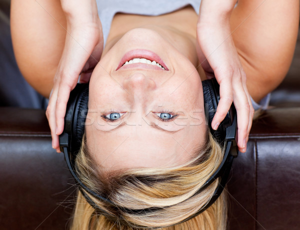 Delighted woman lies on a brown sofa and listen music with headphones