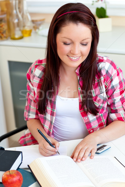 Cute student doing her homework at home in the kitchen Stock photo © wavebreak_media
