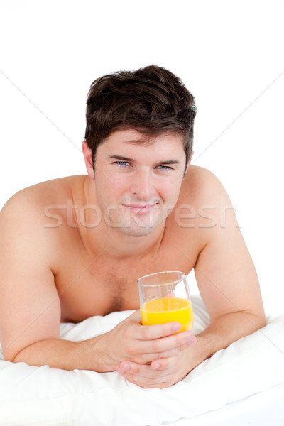 bare-chested man lying on his bed with a glass of orange juice smiling at the camera Stock photo © wavebreak_media