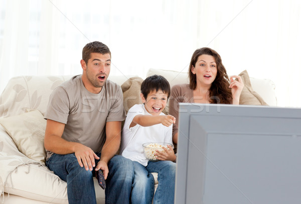 Happy family watching a movie on television together on the sofa at home Stock photo © wavebreak_media