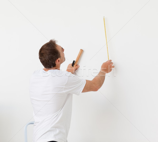 Handsome man looking at a wall with ruler and tools in his new room Stock photo © wavebreak_media