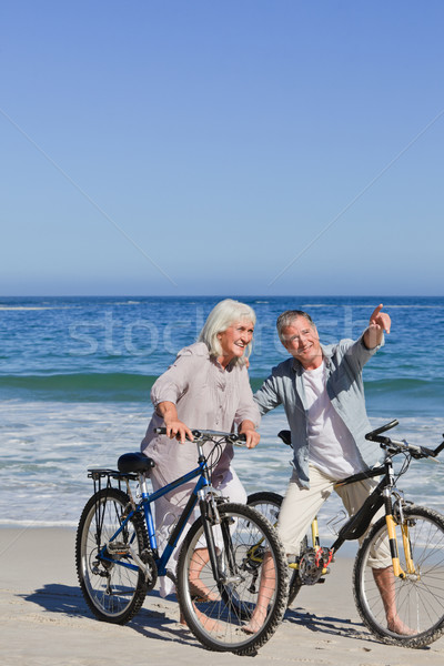 Stock photo: Mature couple with their bikes on the beach