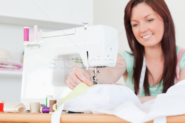 Attractive red-haired female sewing in her living room Stock photo © wavebreak_media