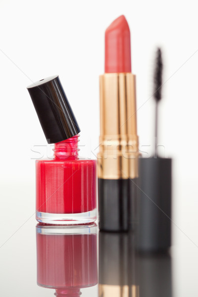 A mascara tube with a pale red lipstick and a red nail polish flask against a white background Stock photo © wavebreak_media