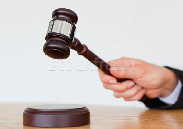 Hand knocking a gavel against a white background Stock photo © wavebreak_media