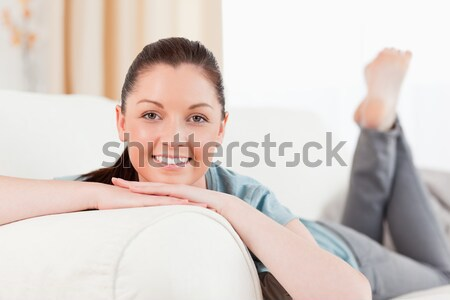 Stock photo: Beautiful woman posing while lying on a sofa in the living room