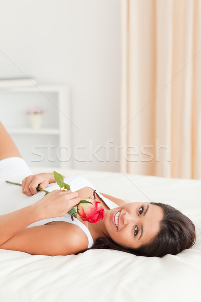 charming woman with rose lying on bed looking into camera in bedroom Stock photo © wavebreak_media