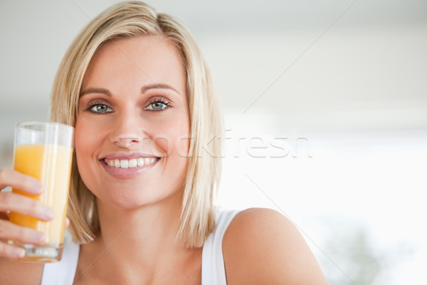 Close up of a smiling woman toasting with orange juice in the kitchen Stock photo © wavebreak_media