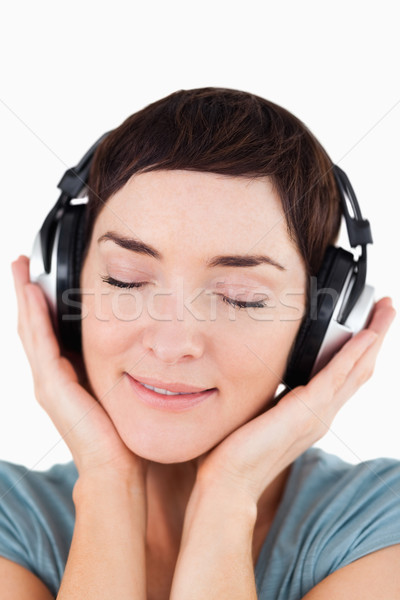 Portrait of a delighted woman listening to music music against a white background Stock photo © wavebreak_media