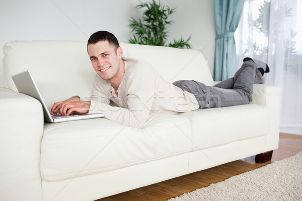 Handsome man lying on a couch with a notebook while looking at the camera Stock photo © wavebreak_media