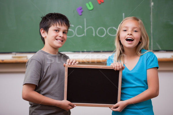 Happy pupils holding a school slate in a classroom Stock photo © wavebreak_media