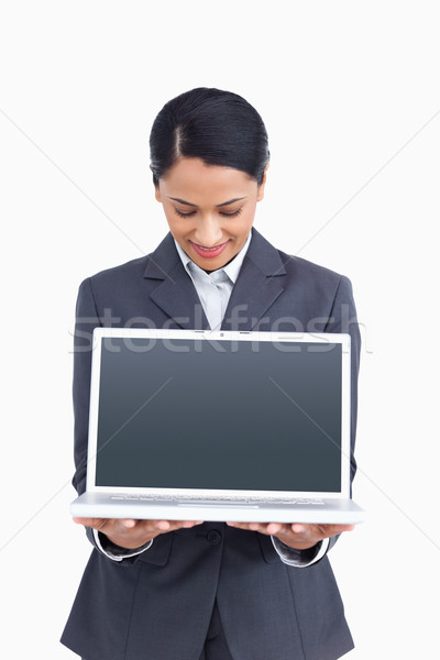 Stock photo: Close up of saleswoman presenting screen of her laptop against a white background