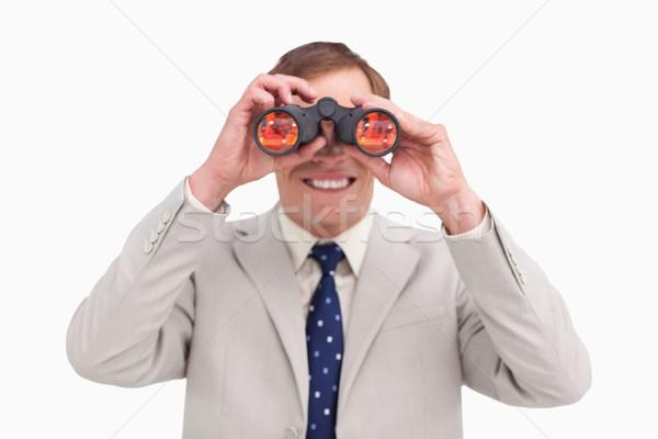 Smiling businessman using binoculars against a white background Stock photo © wavebreak_media