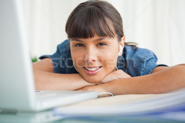 Portrait of a smiling tired student with earphones at her desk Stock photo © wavebreak_media