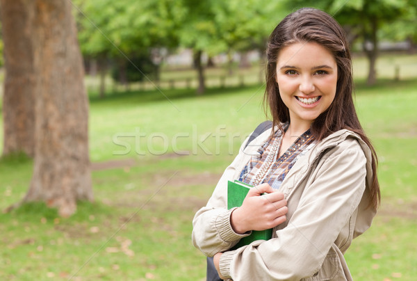 Stock photo: Portrait of a young student holding textbook while posing in a park
