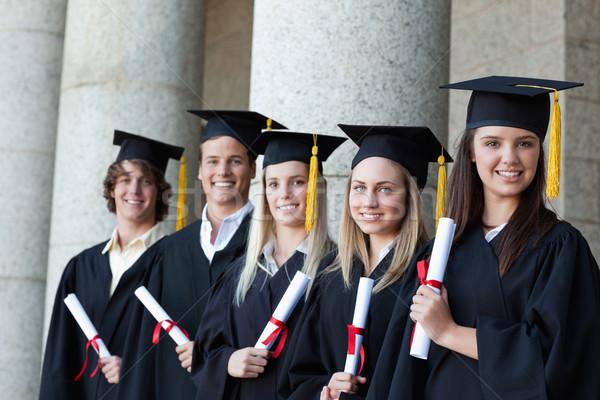 Graduates posing in single line with columns in background Stock photo © wavebreak_media