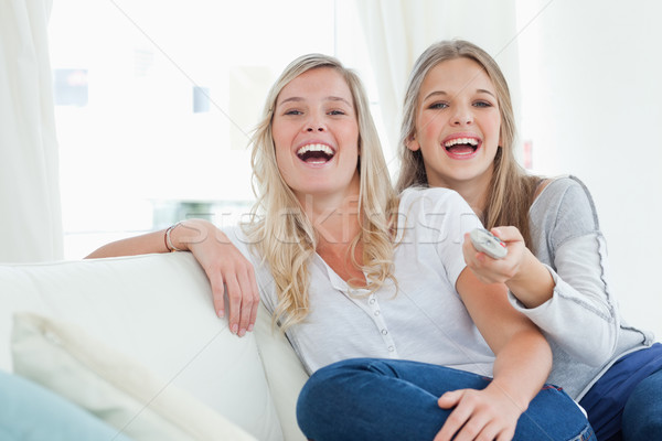 Laughing sisters on the couch as they watch tv and look at the camera  Stock photo © wavebreak_media
