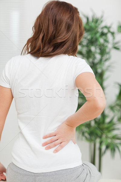 Brunette sitting while massaging her painful back in a room Stock photo © wavebreak_media