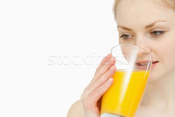 Woman drinking a glass of orange juice while looking away Stock photo © wavebreak_media