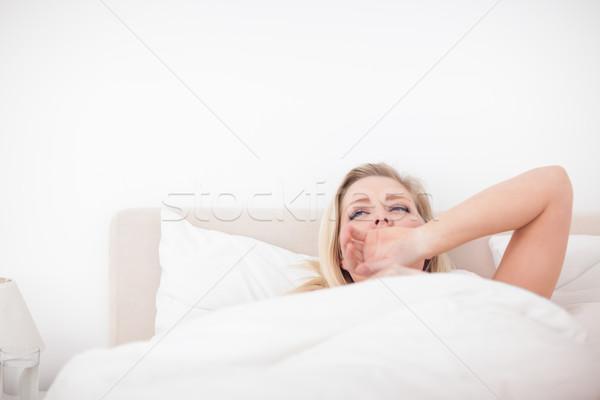 Fiatal szőke nő ásít ágy női hálószoba Stock fotó © wavebreak_media