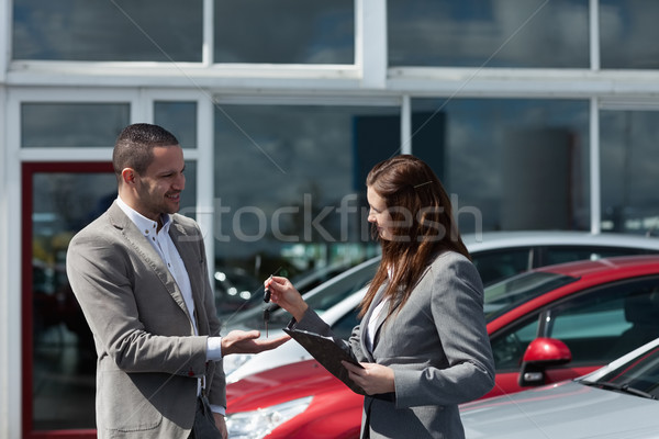 Stock photo: Businesswoman giving car keys to a client in a dealership