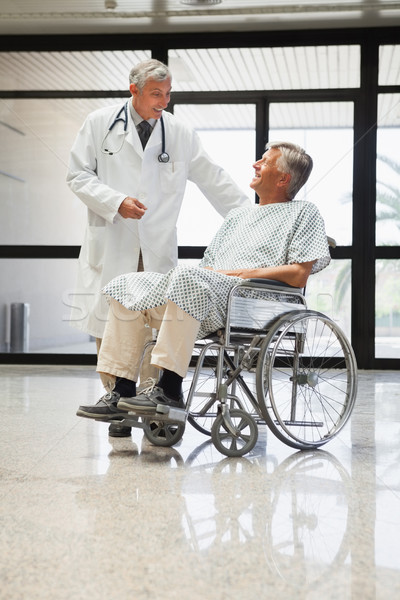 Doctor talking to a man  in a wheelchair smiling  in hospital corridor Stock photo © wavebreak_media