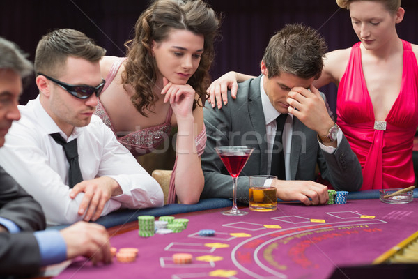 Man losing at poker table with woman comforting him in casino Stock photo © wavebreak_media