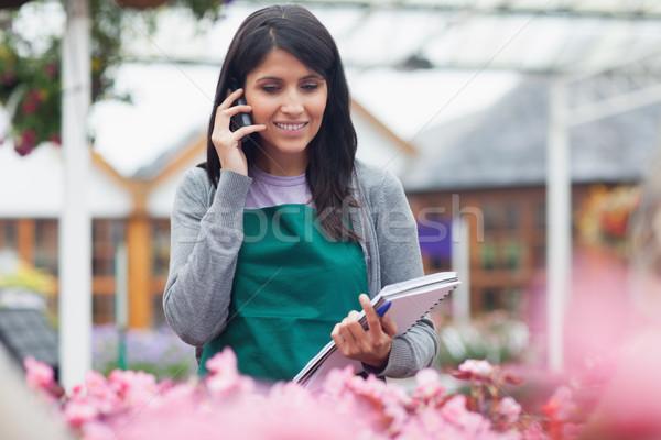 Garden center worker phoning while taking notes on flowers in center Stock photo © wavebreak_media