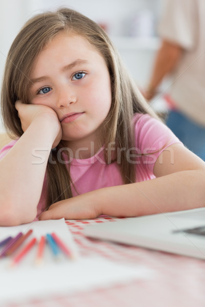Girl sitting at kitchen table looking bored with paper and colouring pencils Stock photo © wavebreak_media