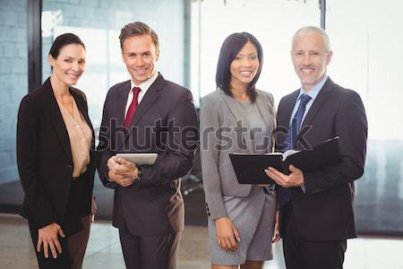 Businessman smiling and three businesswomen speaking Stock photo © wavebreak_media
