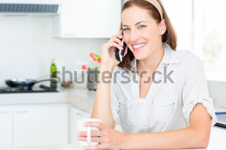 Smiling woman with coffee cup using landline phone in kitchen Stock photo © wavebreak_media