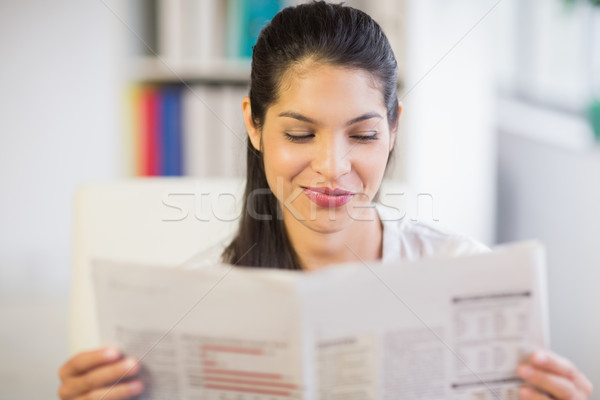 Stock photo: Young businesswoman reading newspaper