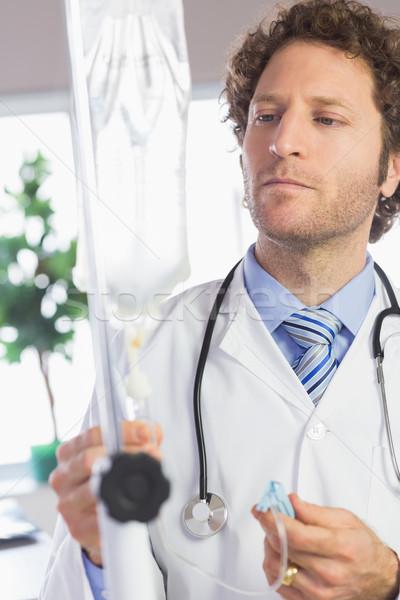 Doctor adjusting IV drip Stock photo © wavebreak_media