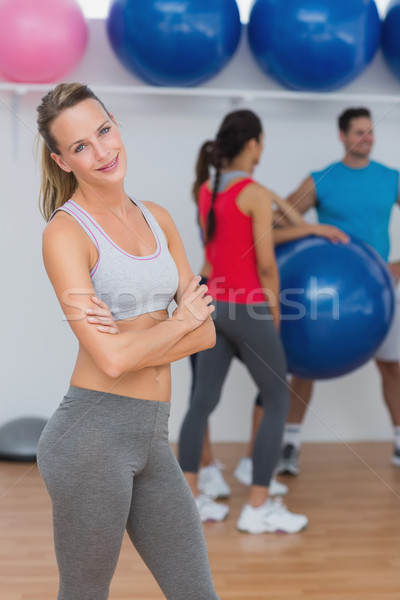 Young woman with friends in background at fitness studio Stock photo © wavebreak_media