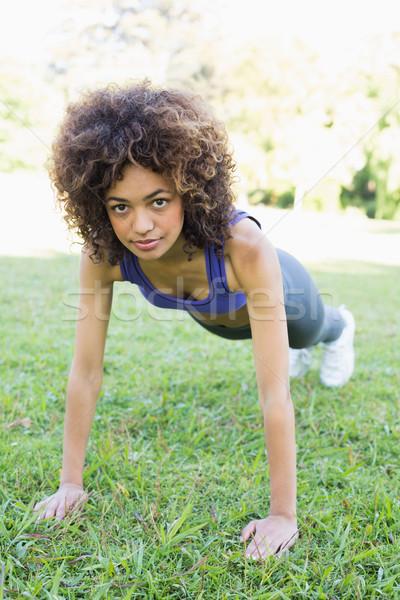 Determined woman doing push ups in park Stock photo © wavebreak_media