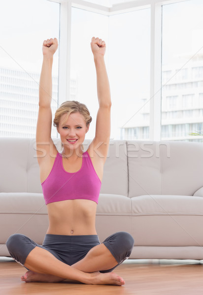 Happy blonde sitting in lotus pose with arms up Stock photo © wavebreak_media