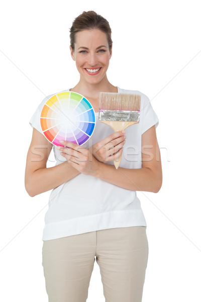 Portrait of a woman with paint samples and paintbrush Stock photo © wavebreak_media