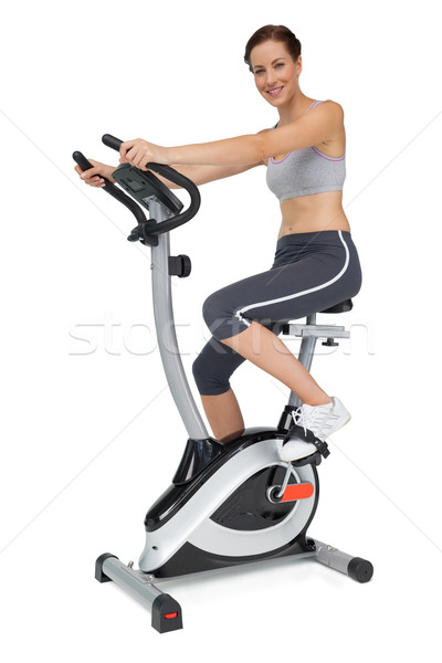 Stock photo: Side view of a beautiful young woman on stationary bike