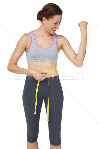 Fit woman measuring waist while flexing muscles Stock photo © wavebreak_media