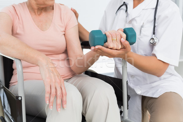 Stock photo: Physiotherapist assisting senior woman to lift dumbbell