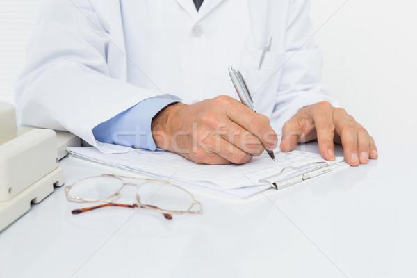 Középső rész férfi orvos ír jelentések közelkép orvosi Stock fotó © wavebreak_media